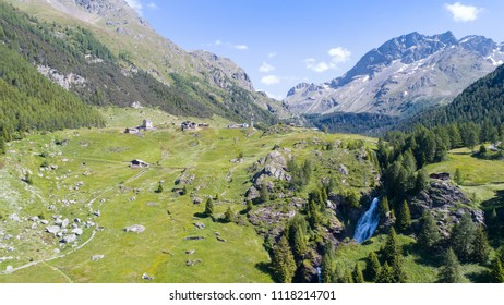 Val Grosina, Valtellina. Waterfall of Eita, green meadows and forest