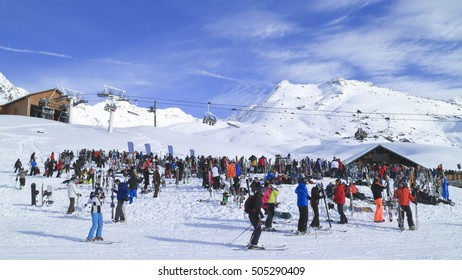 Val Thorens, Alps, 3 Valleys, France, January 29, 2016 : Skiers and snowboarders enjoying apres ski party outside a bar and chairlift with the backdrop of snowy Alps slopes