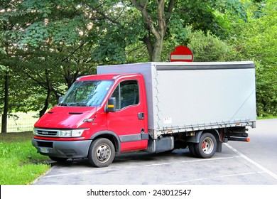 VALAIS, SWITZERLAND - AUGUST 5, 2014: Red cargo truck Iveco Daily at the interurban road.