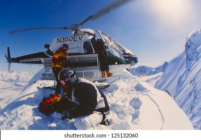 VALDEZ, ALASKA - APRIL 22: Snowboarder Esben Pedersen being dropped of by helicopter onf an isolated peak in the Chugach Mountains on April, 22, 2002. Valdez is the hub for Heli-skiing in Alaska.