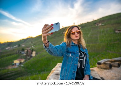 Valdobbiadene, 18/04/19: Beautiful young woman in the Prosecco's hills of Valdobbiadene taking selfie and picture or posing in a sunset light, in the green of the vineyards. Relax on a bench.