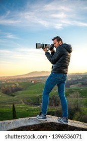 Valdobbiadene, 18/04/2019: Male photographer in the prosecco's hills of Valdobbiadene taking picture with a camera and a very big lens.