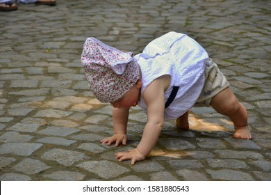 Valdstejn, Bohemian Paradise, Czech Republic - June 6, 2015:  Baby girl in dress with flower scarf is trying to escape from her mother. She is crawling away on the stone pavement for adventure.