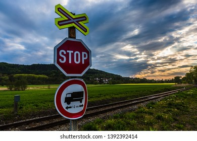Valdstejnsko, Czech Republic - May 5 2019: A red stop sign at the railroad crossing with no entry sign for long vehicles. Rural countryside with green grass and dramatic colorful cloudy sunset sky.
