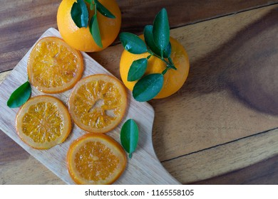 valencia orange slices, candied navel orange slices on a piece of wood which wooden table/flat lay