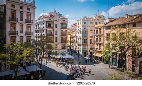 Valencia / Spain - 09 24 2017: A square with summer cafes and people walking in front of the Torres de Serranos or Towers of Serranos medieval gate downtown Valencia city in Spain