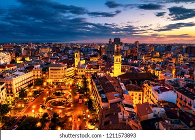 Valencia, Spain. Aerial view of Valencia, Spain at sunset. Illuminated Plaza de la Reina with many cafes and restaurants, car, bus and people traffic. Cloudy colorful sky.