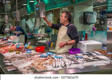 Valencia, Spain - april 17, 2018: Shop owner weighing product in a fish market in the Central Market of the city