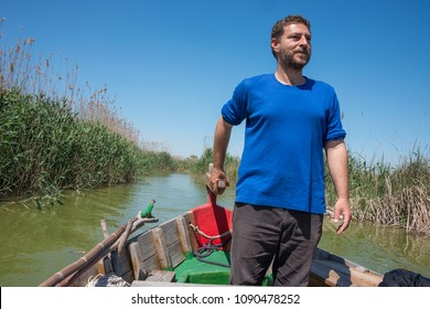 Valencia, Spain - april 17, 2018: Boatman in command of the rudder of a boat for tourist excursions through the waters of the Albufera