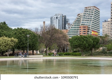 Valencia, Spain - april 17, 2018: Ponds and gardens of the Turia with citizens on bicycles and buildings of modern skyscrapers in the background of the scene