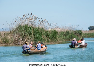 Valencia, Spain - april 17, 2018: Tourists on board traditional boats, tour the waters of the Albufera Natural Park