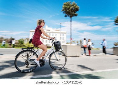 Valencia, Spain - April 29, 2019: Young female tourist biking through the Royal Marina of the Port of Valencia on a sunny spring day.