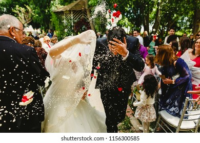 Valencia, Spain - August 11, 2018: Wedding couple after getting married while the guests throw traditional rice in Spain.