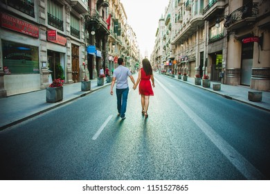 Valencia, Spain - August 2, 2018: Couple walking through the center of an avenue in a city without cars in summer.