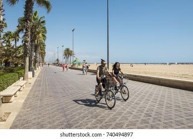 Valencia, Spain - August 21, 2017. People ride bicycles on a sidewalk in Playa de la Malvarrosa beach