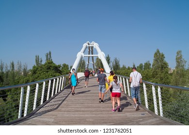 VALENCIA, SPAIN - AUGUST 29, 2018: Visitors are going on bridge into Bioparc Valencia, opened in 2008 as zoo with naturalistic habitats for animals via reproducing various eco-systems of the world.