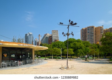 VALENCIA, SPAIN - AUGUST 30, 2018: Landscape in public park Jardines del Turia (Gardens of Turia) of Valencia city, with a modern houses on backgound.