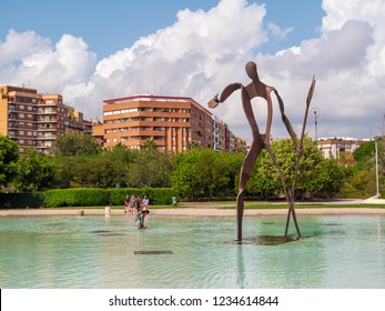 VALENCIA, SPAIN - AUGUST 30, 2018: Landscape in public park Jardines del Turia (Gardens of Turia) of Valencia city, with big iron Neptune statue standing in pond and modern houses on backgound.