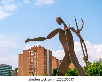 VALENCIA, SPAIN - AUGUST 30, 2018: Landscape in public park Jardines del Turia (Gardens of Turia) of Valencia city, with big iron Neptune statue and modern houses on backgound. Selective focus.