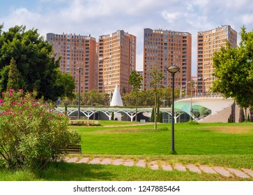VALENCIA, SPAIN - AUGUST 30, 2018: Landscape in public park Jardines del Turia (Gardens of Turia) of Valencia city, with tall modern houses on background.