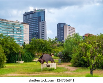 VALENCIA, SPAIN - AUGUST 30, 2018: Landscape in public park Jardines del Turia (Gardens of Turia) of Valencia city, with iron sculptures on foreground and modern buildings on background.