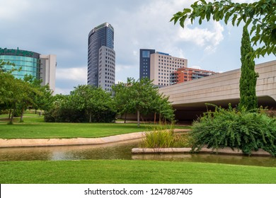 VALENCIA, SPAIN - AUGUST 30, 2018: Landscape in public park Jardines del Turia (Gardens of Turia) of Valencia city, with modern buildings on the background
