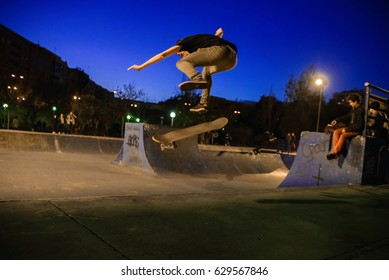 Valencia, Spain - December 29.2015: skateboarder doing a trick jump in the skateboard park at night