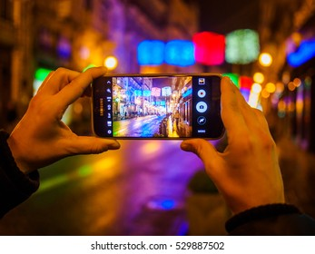Valencia, Spain - December 3 , 2016: Woman hands taking photo of Christmas lights with smartphone