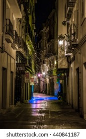 VALENCIA, SPAIN, DECEMBER 31, 2015: people are walking through a narrow street in the old town center of spanish city valencia.