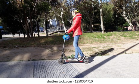 Valencia, Spain - December 5, 2018: Woman driving an electric scooter with helmet around the city as an example of sustainable ecological mobility.