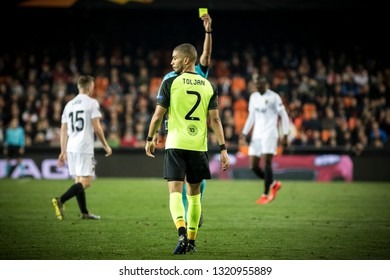 VALENCIA, SPAIN - FEBRUARY 21: Referee shows yellow card to Toljan during UEFA Europa League match between Valencia CF and Celtic FC at Mestalla Stadium on February 21, 2019 in Valencia, Spain