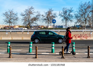 Valencia, Spain - February 28, 2019: Woman moving on her electric scooter transiting a bicycle lane isolated from other vehicles for safety and sustainability.