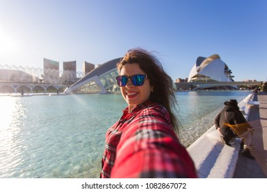 Valencia, Spain, January, 01, 2018, Young woman makes selfie on the background of the Hemisferic building in Valencia, Spain.