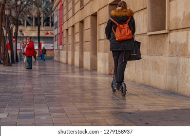 Valencia, Spain - January 06, 2019: Adult woman on Xiaomi Mi Scooter.  Young Woman driving electric scooter in Valencia city center near Colon street.