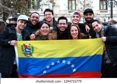 Valencia, Spain - January 23, 2019: People carrying Venezuelan Flag in support of peaceful demonstration.