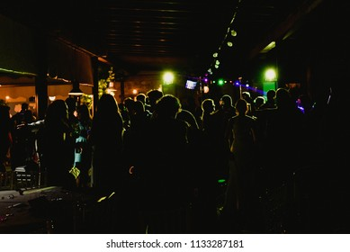 Valencia, Spain - July 10 2018: Backlit night party with lights of lasers and people drinking and dancing on the dance floor