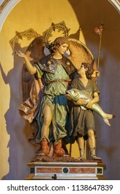 Valencia, Spain - June 15, 2018: Statues of an Angel and Jesus as a Child holding a big Fish, in the Church of Saint Nicholas and Saint Peter Martyr in Valencia, Spain