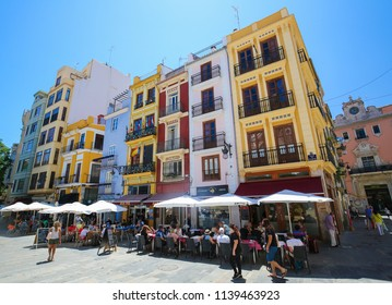 Valencia, Spain - June 15, 2018: Terraces at colorful restaurants at the Calle de Palafox in the center of Valencia, Spain