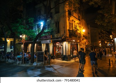 Valencia, Spain - June 2, 2016: Tourists and locals walk in narrow streets with cafe and restaurant at night.