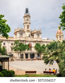 Valencia, Spain - June 2, 2017: View of City Hall in Valencia through Modernisme Plaza with benches. Spanish architecture of neoclassical and baroque gives name to the square, Plaza del Ayuntamiento.