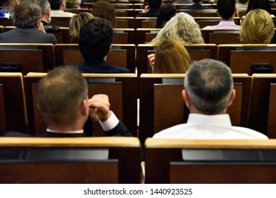 Valencia, Spain - June 20, 2019: Conference attendees carefully attend to the speaker's words sitting in a crowded auditorium.