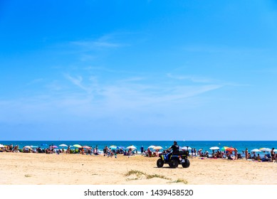 Valencia, Spain - June 23, 2019: Police in quad patrolling a beach full of tourists and holiday makers to avoid thefts and thefts typical of the summer time.