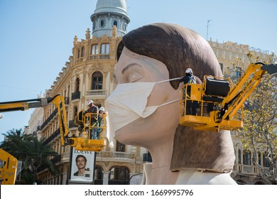 Valencia, Spain; March 11 2020: Cancellation of the most important festivals in Valencia, Las Fallas, due to the coronavirus COVID-19. Operators are installing a mask at the head of a ninot of a Falla