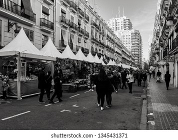 Valencia, Spain, March 14, 2019. Black and white photograph of the street convent of Jerusalem, during the Fallas festival, with many people visiting the street market of the festivities.