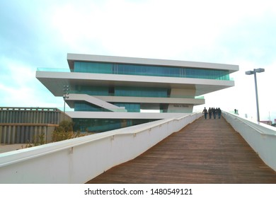 Valencia, Spain - March 15th 2015 - View Looking Up the Pathway at Four People Walking from Behind to the Deck of a Modern Beach Side Building