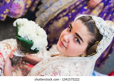 Valencia, Spain - March 17, 2019: Portrait of falleras women, wearing the traditional costume of Fallas on the day of the offering to the Virgin during the parade through the streets of Valencia.