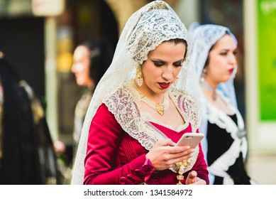 Valencia, Spain - March 17, 2019: Falleras using her mobile phone with her typical dress with petticoat and bodice, while they wait their turn for the offering in the Plaza de la Virgen de Valencia.