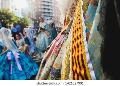 Valencia, Spain - March 17, 2019: Banda and Valencian flag decorating the typical Valencian fallera dress, worn by the beautiful women of Fallas.