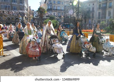 Valencia, Spain - March 18, 2019: Women and children in colorful traditional dresses participate in L'Ofrena de flors (flower offering to Virgin Mary, Our Lady of Forsaken) during Las Fallas events.