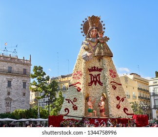 Valencia, Spain, March 20, 2019. Festival of las fallas. People enjoying the city, in the Plaza de la Virgen, where the cathedral is located. Statue of the virgin with the mantle made of flowers.